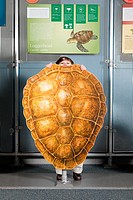 Boy standing behind loggerhead sea turtle shell