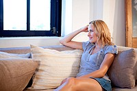 Woman sitting on sofa and looking away