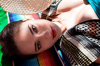 Woman lying on ethnic style blanket, close up