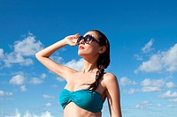 Woman wearing sunglasses shielding eyes