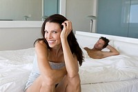 Woman sitting on bed, man sleeping