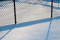 Wire mesh fence in snow, abstract