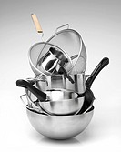 Cooking utensils, shot on white background. There are some saucepans, pans and colanders in a stack. The photograph was taken in a studio and its fram...