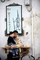 A man carries in arms his son in front of an advertisement drawing the shape of a penitent during an Easter Holy Week procession in Carmona village, S...
