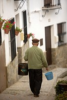 A senior man carrying buckets walks in a street of El Gastor village in the Sierra de Grazalema Natural Park, Cadiz province, Andalusia, Spain, april ...