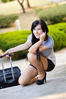 Attractive young woman is squatting next to a travel suitcase