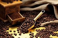 Coffee mill, ground coffee and coffee beans in a golden scoop