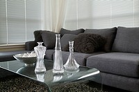 decanters on a table by a sofa in a living room
