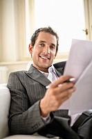 Businessman holding document, smiling, portrait