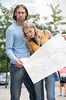 Young couple holding map