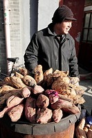 A man selling traditional Beijing style baked yams on the street of Nan Luo Gu Xian South Luo Gu Lane the new trendy area for the bars, restaurants an...