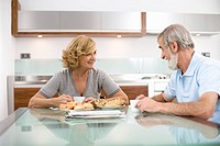 Senior couple having breakfast at dinning table, smiling