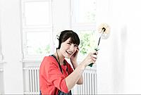 Germany, Cologne, Young woman listening music and painting with roll brush