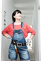 Germany, Cologne, Young woman with hammer renovating apartment