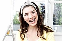 Germany, Cologne, Close up of young woman at renovating apartment, smiling, portrait