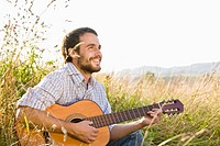 Mid adult man playing guitar in field