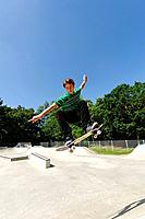 Germany, Duesseldorf, Young man performing tricks with skateboard in skatepark