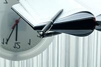 Close up of notebook, pen and clock with reflection on table
