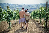 embracing couple strolls through the vineyards