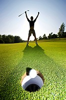 A Golfer celebrating a succesful putt