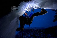 Ice Climbing at night on the edge of a cave