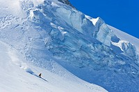 A snowboarder riding fast on an icy glacier