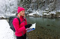 Woman map reading by snowy riverside