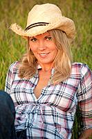 35 year old blond woman wearing jeans and a straw hat sitting on grass smiling at camera