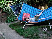 Canada, Ontario, Windsor. Nine year old girl on hammock reading when a dog approaches