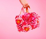 red flowers fashion bag in woman hand on pink background