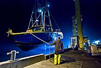 Commercial fishing boat being hoisted out of Pacific Ocean in Port Orford, Oregon, all boats are stored on pier, not moored in water