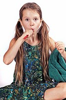 eight year old girl with a toothbrush and a towel to clean the teeth