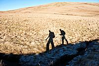 Shadow of two hikers on grassland, Brecon Beacons national park, Wales
