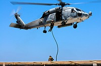 LONG BEACH, Calif  July 28, 2011 A U S  Navy SEAL fast ropes from an HH-60H Sea Hawk helicopter assigned to the High Rollers of Helicopter Sea Combat ...