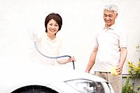 Senior couple washing car, using hose and sponge