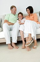 Mid adult couple with their son sitting on a couch and smiling