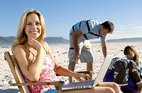 Portrait of a mid adult woman using a laptop with her family playing on the beach