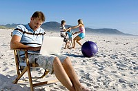 Mid adult man using a laptop with his family playing on the beach