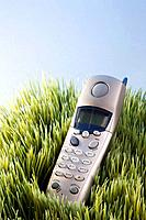 Studio shot of landline telephone placed in grass.