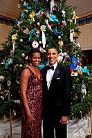 President and Michelle Obama pose in front of the Official White House Christmas Tree Dec. 5 2010. Michelle wears a scarlet floral sequined gown by Na...