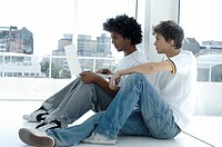 Close_up of two young men sitting on the floor and using a laptop