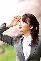 Businesswoman in a field shielding her eyes