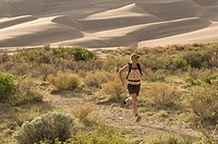 Woman running through sand dunes, Great Sand Dunes National Park, Alamosa, Colorado.