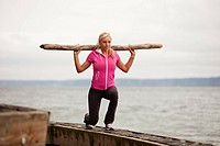 A fit woman exercises using found beach materials.