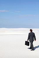 USA, New Mexico, Whitesands, Man wearing suit walking on desert