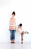 Portrait of girl and woman standing hand in hand, white background