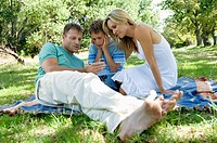 Mid adult couple sitting with their son in a park and looking at an MP3 player