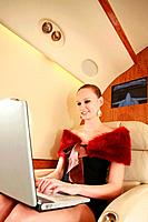 Woman using laptop on private jet