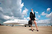 Businesswoman at runway with private jet in the background