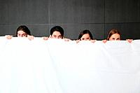 Men and women standing behind comforter, looking at camera